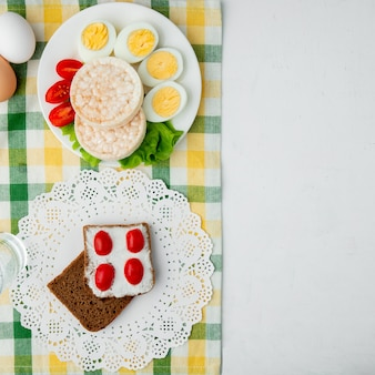 Top view of crispbreads and slice of bread smeared with cottage cheese on cloth and white background with copy space