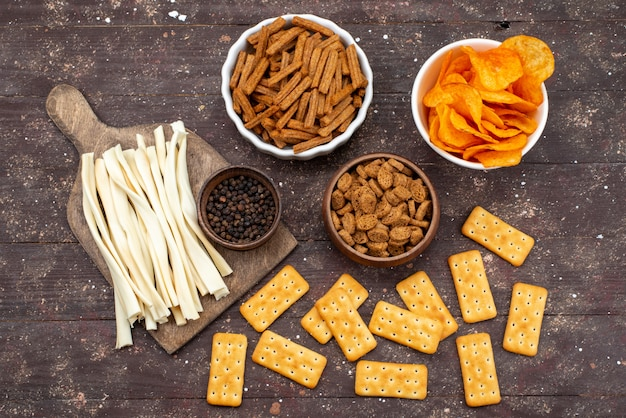 Вид сверху чипсы и чипсы вместе с крекерами на коричневом деревянном столе.
