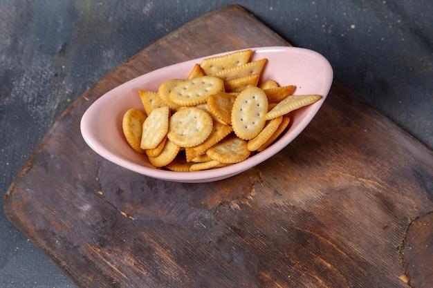 Чипсы и крекеры, вид сверху на розовой тарелке на деревянном столе и на сером фоне фото закусок с хрустящими крекерами