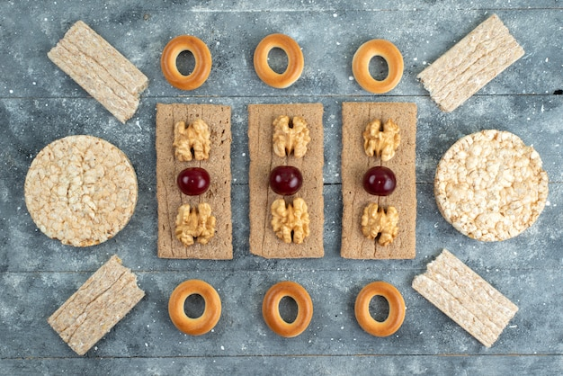 Top view crisps and crackers with walnuts and cherries on grey