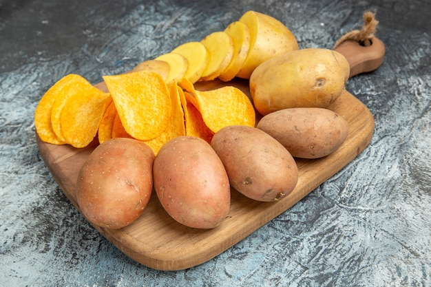 Top view of crispy chips and uncooked potatoes on wooden cutting board on gray background