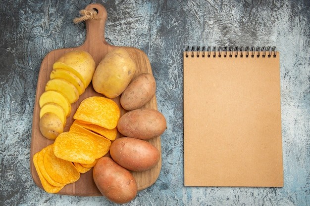 Top view of crispy chips and uncooked potatoes on wooden cutting board and notebook on gray background