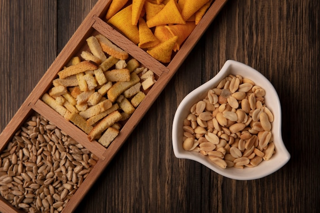 Top view of crispy cone shape corn snacks on a wooden divided plate with shelled sunflower seeds with pine nuts on a bowl on a wooden table