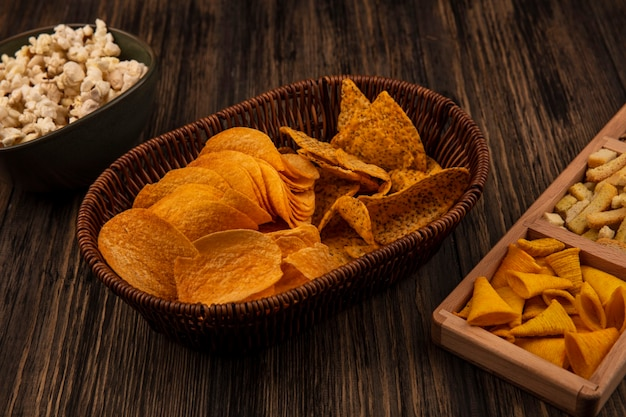 Top view of crispy cone shape corn snacks on a wooden divided plate with shelled sunflower seeds with spicy chips on a bucket with popcorns on a bowl on a wooden table