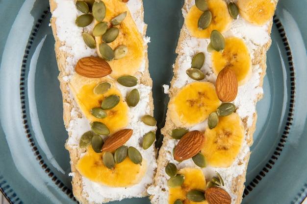 Vista dall'alto di cracker croccanti con crema di formaggio, fette di banana, mandorle e semi di zucca su un piatto su legno bianco