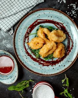 Vista dall'alto di anelli di calamari fritti croccanti guarniti con salsa teriyaki e sesamo