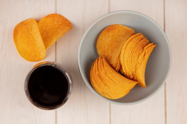Top view of crispy potato chips on a bowl with a glass of cola on a beige wooden table
