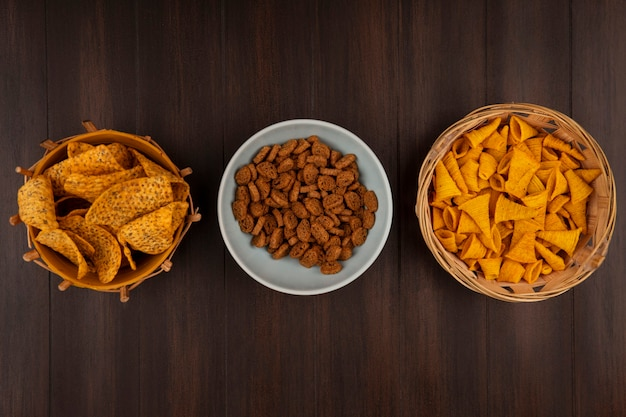 Top view of crispy tasty rye rusks on a bowl with spicy chips on a bucket with corn snacks on a bucket on a wooden table Free Photo