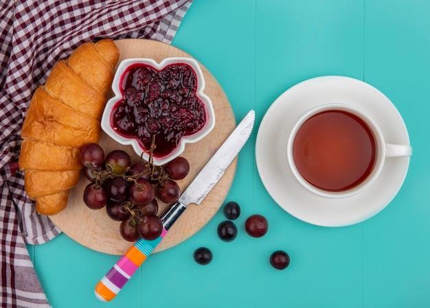 Vista dall'alto di croissant e marmellata di lamponi nella ciotola uva con il coltello sul tagliere sul panno plaid e tazza di tè su sfondo blu