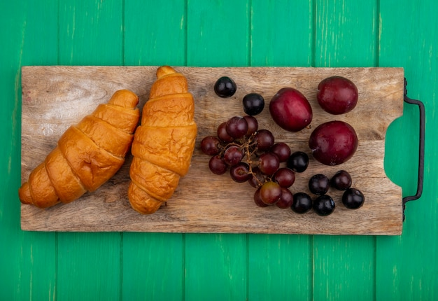 Top view of croissants and grape pluots sloe berries on cutting board on green background