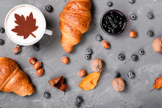 Top view of croissants, jam and coffee breakfast