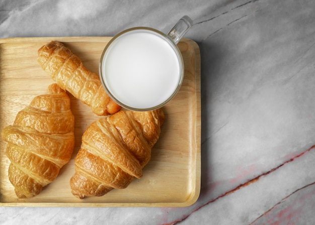 Top view croissants and milk on marble surface.