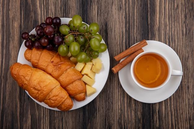 Vista dall'alto di croissant con uva e fette di formaggio nella piastra con tazza di hot toddy con cannella sul piattino su sfondo di legno