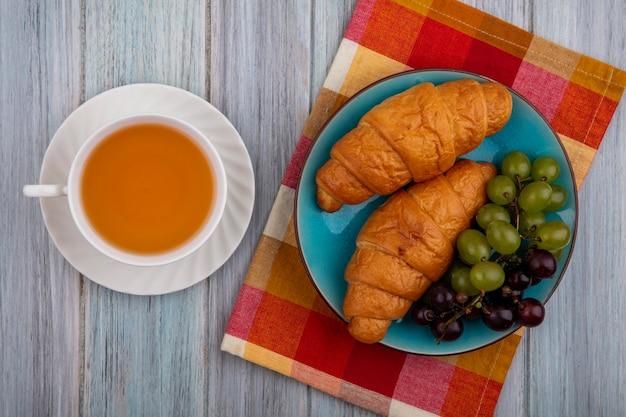Vista dall'alto di croissant con l'uva nel piatto sul panno plaid e tazza di toddy caldo su fondo di legno