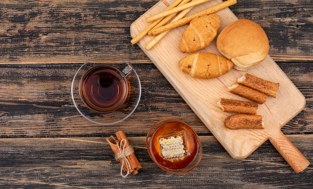 Top view of croissants with tea and honey on dark wooden surface horizontal