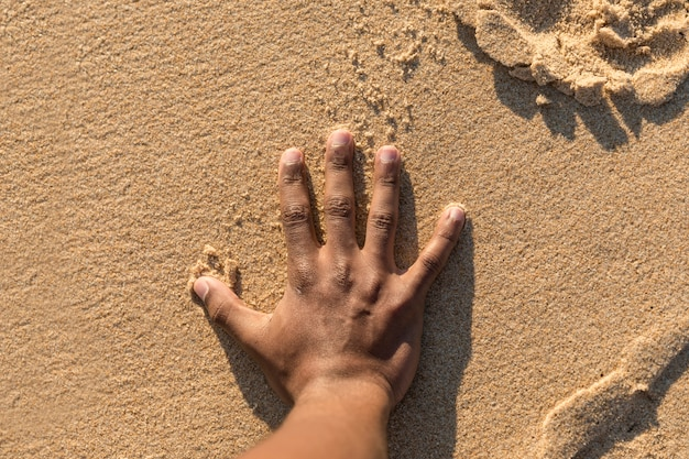 Top view of crop hand on sand