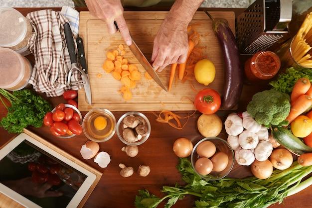Vista superiore delle mani potate della carota di taglio irriconoscibile del cuoco senior che cucina stufato di verdure