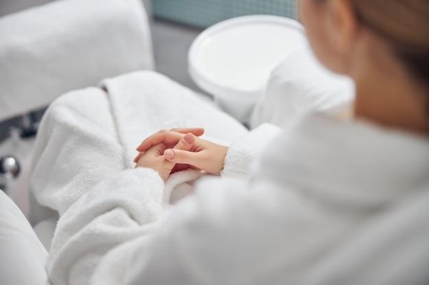 페디큐어 의자에 앉아 메시지 목욕에 발을 들고 여성의 상위 뷰 자른 머리