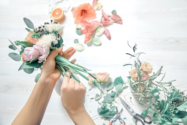 Top view cropped image of female florist arranging a bouquet with flowers use tools on white woodem background. flowers delivery. copy space. workplace and professional concept
