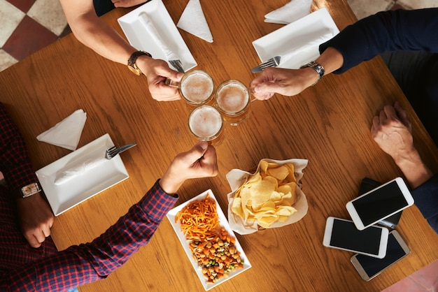 Top view of cropped people toasting for friendship with beer