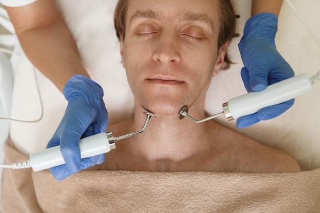 アンチエイジングスキンケア治療を受けている成熟した男性のトップビュークロップドショット