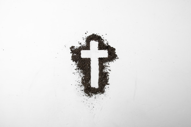 Top view of cross shape with dark soil on white