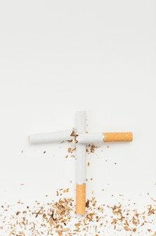 Top view of cross sign made from broken cigarette against white backdrop