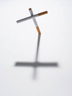 Top view of cross sign made from cigarette with it shadow on isolated on white background