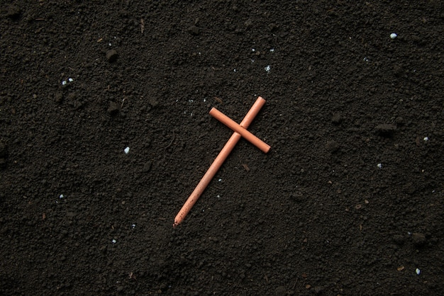 Top view of cross on soil grim reaper devil death