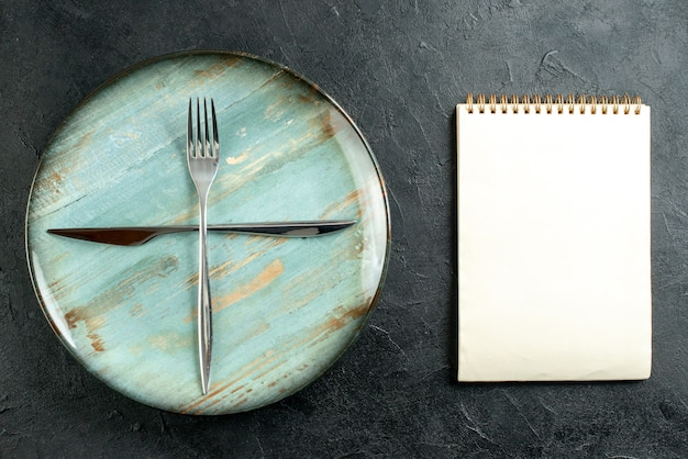 Top view crossed fork and knife on cyan round plate notebook on dark table