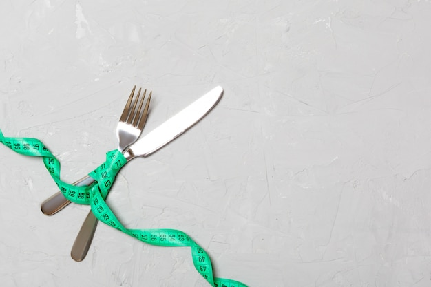 Top view of crossed knife and fork connected by measuring tape