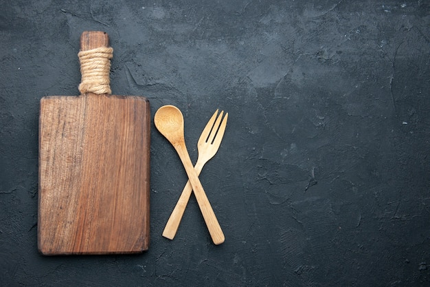 Top view crossed wooden spoon and fork serving board on dark table with copy place