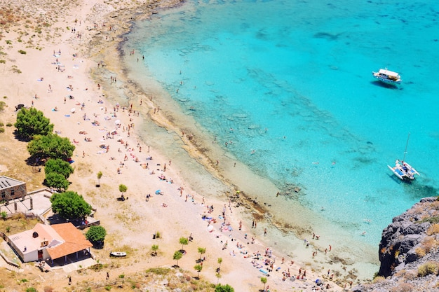 Top view of the crowded beach with white sand and turquoise sea. a popular haven for tourists.
