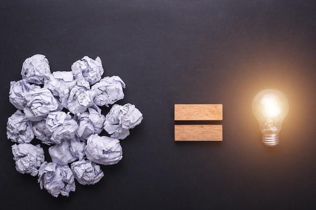トップビューは黒い石ボード上の白い紙と電球を詰めた