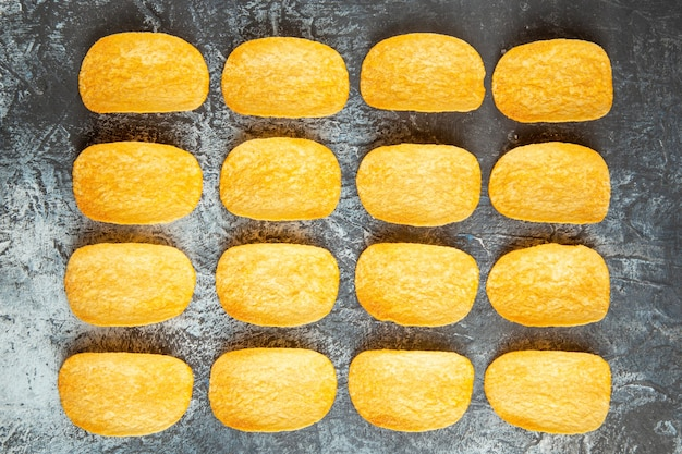 Top view of crunchy baked five chips lined up in rows on gray background