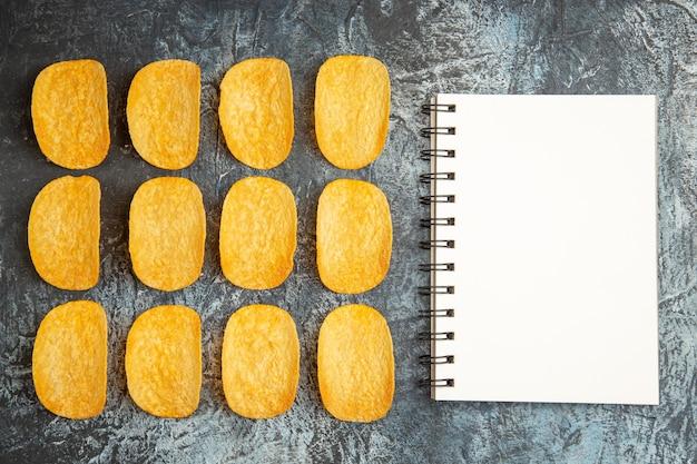 Vista dall'alto di cinque patatine al forno croccanti allineate in righe e taccuino sul tavolo grigio