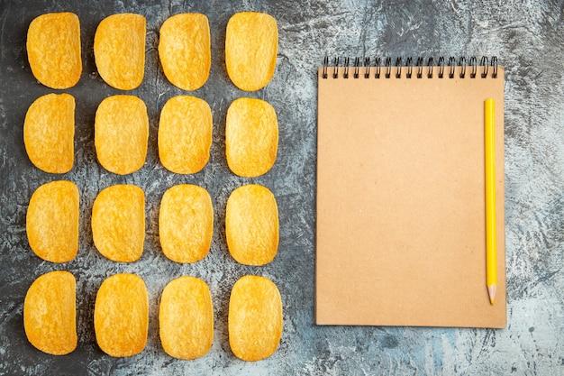 Vista dall'alto di cinque patatine al forno croccanti allineate in righe e taccuino con penna su sfondo grigio