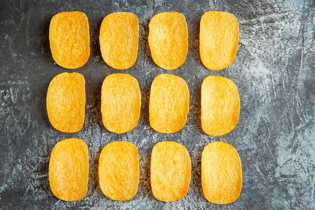Vista dall'alto di cinque patatine al forno croccanti allineate in righe e taccuino con la penna sul tavolo grigio
