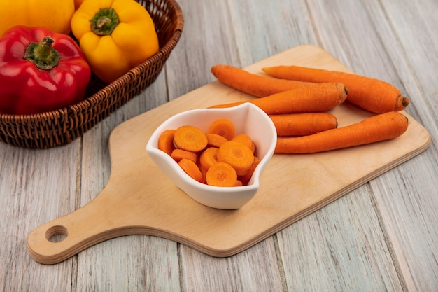 Top view of crunchy carrots on a wooden kitchen board with colorful bell peppers on a bucket on a grey wooden background