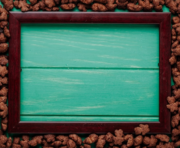 Top view of crunchy chocolate corn flakes arranged around an empty picture frame with copy space on green wooden background