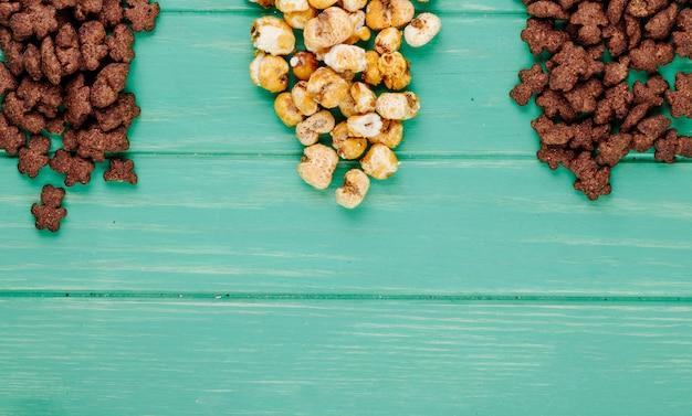 Top view of crunchy chocolate corn flakes and caramel popcorn on green background with copy space