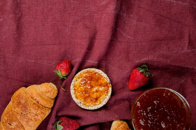 Top view of crunchy crispbread and strawberries with peach jam on bordo cloth surface with copy space