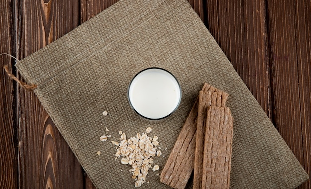 Top view crunchy crispbread with oatmeal and glass of milk on wooden table
