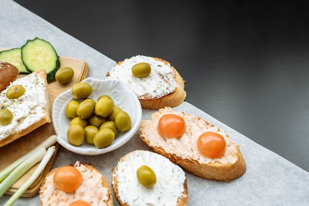 Top view of a crusty baguette slices with cherry tomatoes, cucumbers and green olives, cream cheese.