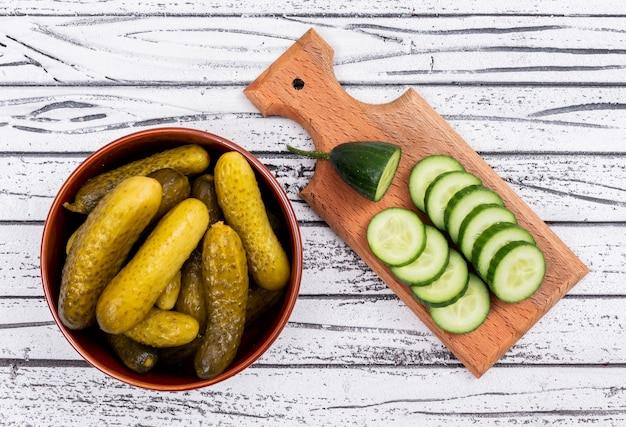 Top view cucumber pickled in bowl and fresh sliced on cutting board on white wooden