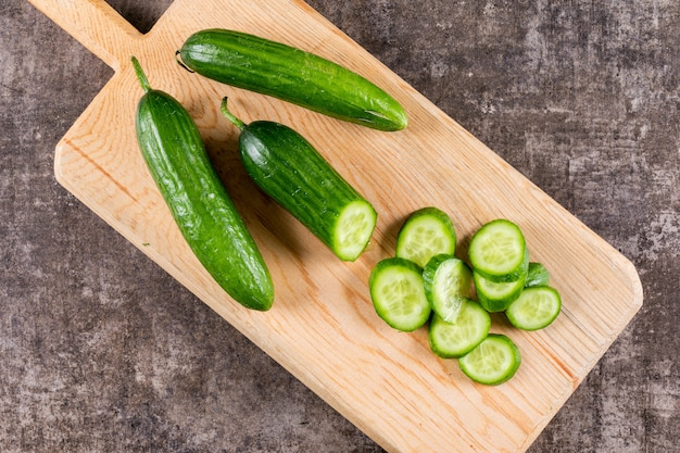 Top view cucumber sliced on wooden cutting board on brown stone  horizontal 1