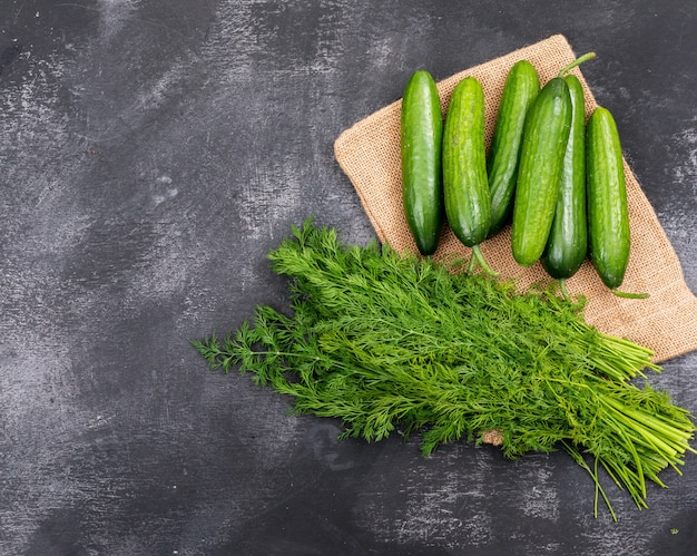 Top view cucumber with dill on linen cloth on black stone  horizontal