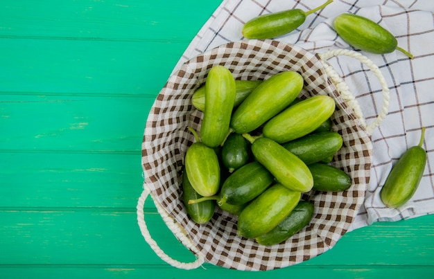Top view of cucumbers in basket with other ones on cloth and green surface with copy space