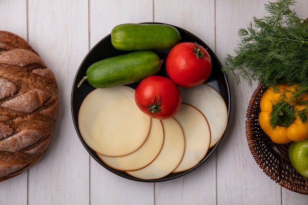 Top view cucumbers with bell peppers and dill in a basket with smoked cheese and tomatoes with a loaf of bread  on a white background