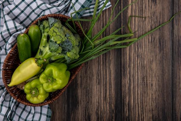Вид сверху огурцы с зеленым перцем, брокколи и зеленым луком в корзине на деревянном фоне